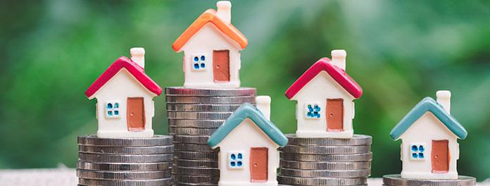 Casas encima de monedas. Concepto de impuestos en reforma de comunidad de vecinos